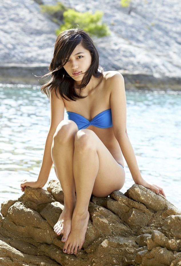 風に吹かれながら岩に座る細い手足が綺麗な川口春奈