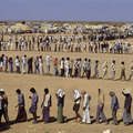 "Refugees in the desert. The Sha-alaan One camp, is the worst camp. They have orderly food lines with thousands of refugees waiting calmly for food distribution from the ""Charitas"" charity organization. Jordan, 1990."