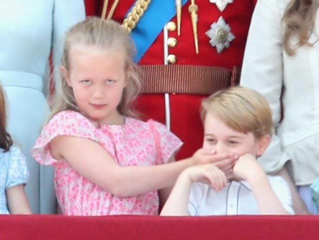 はとこのサヴァンナ・フィリップスに口をふさがれるジョージ王子/エリザベス女王の誕生日パレードにて (C)Getty Images